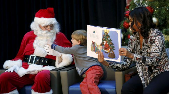 "Patient Stephen Orzechowski, 6, reaches out for Santa's beard as First Lady Michelle Obama reads ""T'was the Night Before Christmas"" to children during her visit to Children's National Health System in Washington, December 14, 2015. REUTERS/Kevin Lamarque"