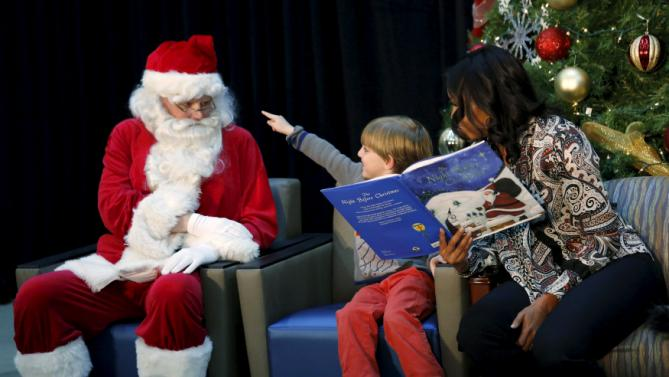 "Patient Stephen Orzechowski, 6, points to Santa Claus as First Lady Michelle Obama reads ""T'was the Night Before Christmas"" to children during her visit to Children's National Health System in Washington, December 14, 2015. REUTERS/Kevin Lamarque"
