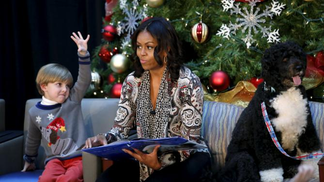 "Patient Stephen Orzechowski, 6, raises his hand as First Lady Michelle Obama reads ""T'was the Night Before Christmas"" to children during her visit to Children's National Health System in Washington, December 14, 2015. On the right is the Obama's dog Bo. REUTERS/Kevin Lamarque"