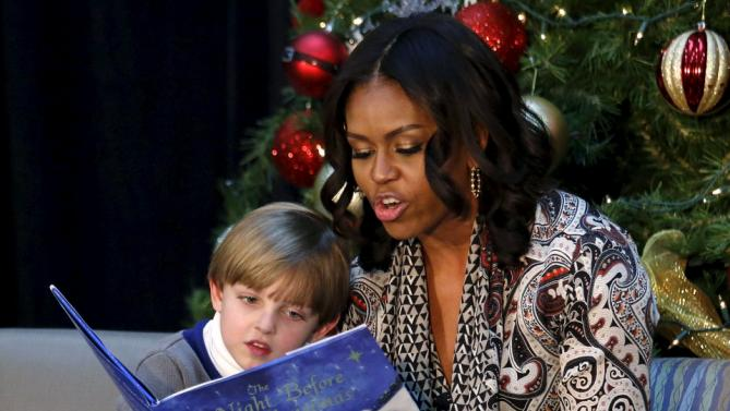"Patient Stephen Orzechowski, 6, leans in as First Lady Michelle Obama reads ""T'was the Night Before Christmas"" to children during her visit to Children's National Health System in Washington, December 14, 2015. REUTERS/Kevin Lamarque"