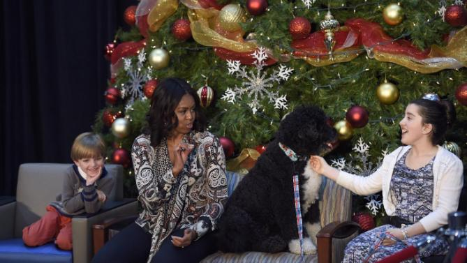 "First lady Michelle Obama, sitting with Stephen Orzechowski, 5, left, Bo Obama, second from right, and Luna Fera, 11, answers questions after reading ""Twas the Night Before Christmas"" to a group of children at the Children's National Health System in Washington, Monday, Dec. 14, 2015. Her appearance continued a first lady tradition that dates back more than 60 years to Bess Truman, who first brought holiday cheer to children not well enough to leave the hospital in time for Christmas. (AP Photo/Susan Walsh)"