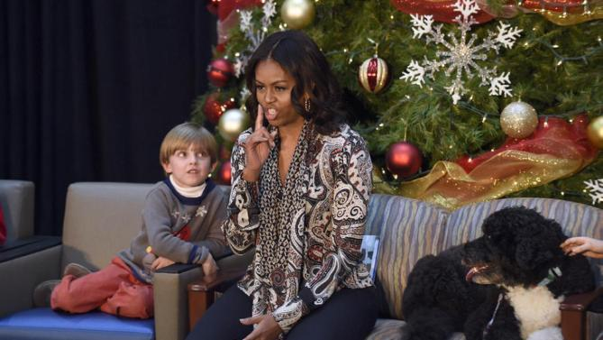 First lady Michelle Obama quiets the audience as she answers the question on what she is going to get President Barack Obama for Christmas during a visit to the Children's National Health System in Washington, Monday, Dec. 14, 2015. Stephen Orzechowski, 5, sits at left, and Bo Obama is at right. Her appearance continued a first lady tradition that dates back more than 60 years to Bess Truman, who first brought holiday cheer to children not well enough to leave the hospital in time for Christmas. (AP Photo/Susan Walsh)