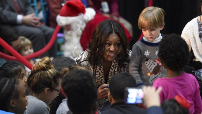 "First lady Michelle Obama greets children after reading ""Twas the Night Before Christmas"" to a group of children at the Children's National Health System in Washington, Monday, Dec. 14, 2015. Her appearance continued a first lady tradition that dates back more than 60 years to Bess Truman, who first brought holiday cheer to children not well enough to leave the hospital in time for Christmas. (AP Photo/Susan Walsh)"