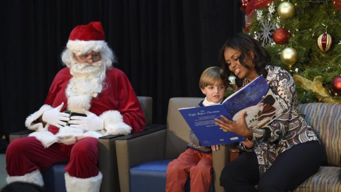 "First lady Michelle Obama sits with Stephen Orzechowski, 5, center, and Santa Claus as she reads ""Twas the Night Before Christmas"" to a group of children at the Children's National Health System in Washington, Monday, Dec. 14, 2015. Her appearance continued a first lady tradition that dates back more than 60 years to Bess Truman, who first brought holiday cheer to children not well enough to leave the hospital in time for Christmas. (AP Photo/Susan Walsh)"
