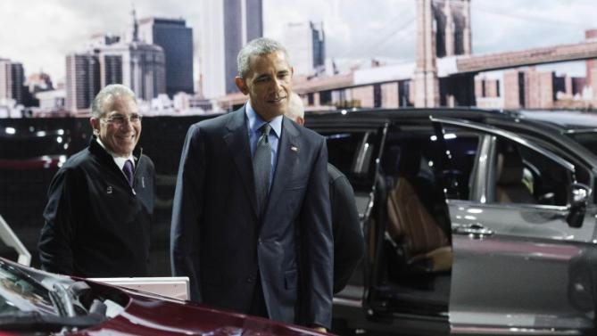 President Obama looks over the Chrysler Pacifica minivan, with NAIAS chairman Paul Sabatini at the North American International Auto Show in Detroit, Wednesday, Jan. 20, 2016. (Daniel Mears/Detroit News via AP, Pool)