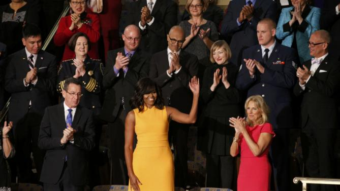 U.S. first lady Michelle Obama waves from her box in the gallery with Connecticut Governor Dannel Malloy (L) on one side and a symbolic empty seat for victims of gun violence between her and Dr. Jill Biden (R) while attending U.S. President Barack Obama's State of the Union address to a joint session of Congress in Washington, January 12, 2016. Behind the first lady are (L-R) veteran and Dream Act immigrant Oscar Vazquez, Seattle Police Chief Kathleen O'Toole, Ryan Reyes, the partner of one of the victims of the San Bernardino shootings, Microsoft CEO Satya Nadella, community college student Jennifer Bragdon and Air Force Staff Sgt. Spencer Stone, who helped stop an attack on Paris bound train in August, and Jim Obergefell, the named plaintiff in the U.S. Supreme Court same-sex marriage ruling, REUTERS/Kevin Lamarque