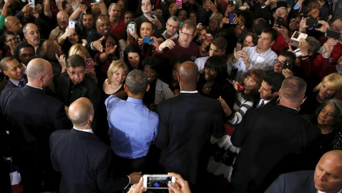 U.S. President Barack Obama (in blue shirt, back to camera) greets people in the audience after his remarks on the U.S. auto industry at the United Auto Workers-General Motors (UAW-GM) Center for Human Resources in Detroit, Michigan January 20, 2016. REUTERS/Jonathan Ernst
