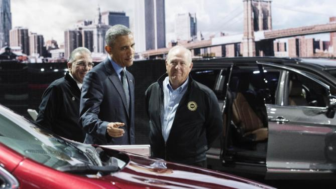 President Obama looks over the Chrysler Pacifica minivan, with NAIAS chairman Paul Sabatini, far left, and UAW President Dennis Williams at the North American International Auto Show in Detroit, Wednesday, Jan. 20, 2016. (Daniel Mears/Detroit News via AP, Pool)