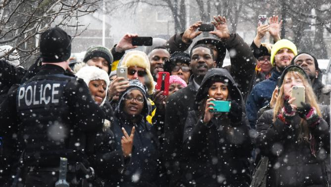 As the snow falls, surprised onlookers try to see President Barack Obama as he visits retail store Shinola in Detroit, Wednesday, Jan. 20, 2016. (Daniel Mears/Detroit News via AP, Pool)