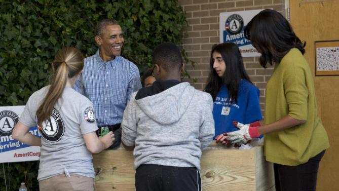 President Barack Obama, second from left, and first lady Michelle Obamam right, assemble a garden bed as they participate in a service project at Leckie Elementary School in Washington, Monday, Jan. 18, 2016, to commemorate Martin Luther King, Jr. Day of Service. (AP Photo/Carolyn Kaster)