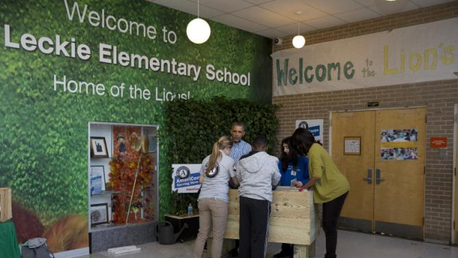 President Barack Obama, second from left, and first lady Michelle Obama, right, assemble a garden bed as they participate in a service project at Leckie Elementary School in Washington, Monday, Jan. 18, 2016, to commemorate Martin Luther King, Jr. Day of Service. (AP Photo/Carolyn Kaster)