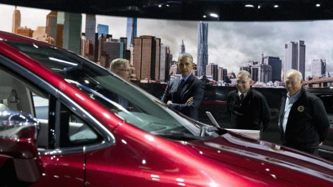 President Barack Obama stops by the Chrysler exhibit during his visit to the 2016 North American International Auto Show in Detroit, Wednesday, Jan. 20, 2016. With him, from left are, Mitch Clauw, Fiat Chrysler's vice president of vehicle engineering, Paul Sabatini, North American International Auto Show chairman, and Dennis Williams, president of the UAW. (AP Photo/Carolyn Kaster)