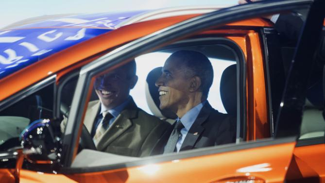 President Obama sits in the 2017 Chevrolet Bolt EV, an all-electric vehicle with an estimated range of 200 miles on a single charge, while touring the North American International Auto Show in Detroit, Wednesday, Jan. 20, 2016. The man at left is unidentified. (Daniel Mears/Detroit News via AP, Pool)
