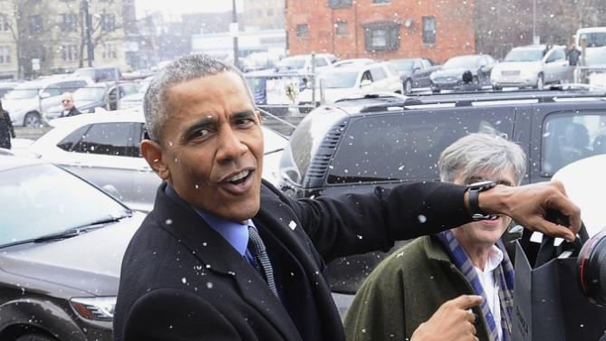 """President Barack Obama responds to a bystander after visiting retail store Shinola in Detroit, Wednesday, Jan. 20, 2016. Someone yelled out, """"Did you buy a watch?"""" Obama said, """"I already have one,"""" and pointed to the watch on his wrist. (Daniel Mears/Detroit News via AP, Pool)"""
