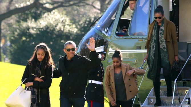 U.S. President Barack Obama waves as he with first lady Michelle Obama (R) and their daughters Malia (L) and Sasha walk on the South Lawn of the White House in Washington January 3, 2016. The Obama family returned from Hawaii, the president's home state, after concluding a 15-day holiday vacation. REUTERS/Yuri Gripas