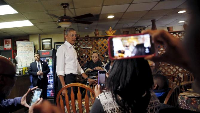 """U.S. President Barack Obama talks to costumers as he orders a """"poor boy sandwich"""" at Poor Boy Lloyd's Restaurant in downtown Baton Rouge, Louisiana, January 14, 2016. REUTERS/Carlos Barria"""