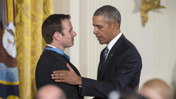 President Barack Obama talks to Medal of Honor recipient Senior Chief Special Warfare Operator Edward Byers during a ceremony in the East Room of the White House in Washington, Monday, February 29, 2016. Navy Senior Chief Byers received the Medal of Honor for his courageous actions while serving as part of a team that rescued an American civilian being held hostage in Afghanistan on December 8-9, 2012. (AP Photo/J. Scott Applewhite)