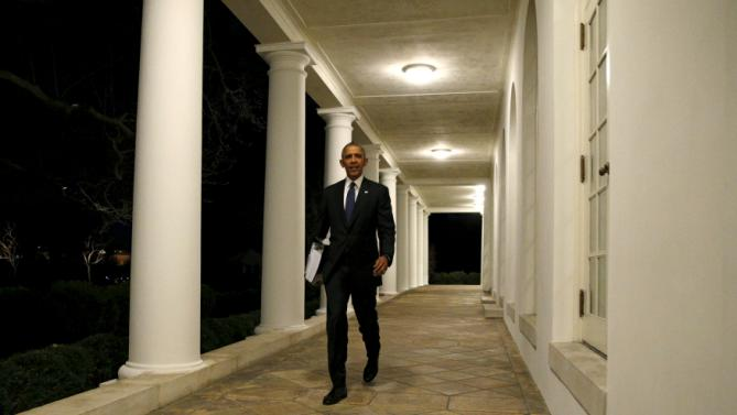U.S. President Barack Obama carries a binder containing material on potential Supreme Court nominees as he walks towards the residence of the White House in Washington February 19, 2016. This weekend, Obama is expected to review material his team has prepared for him on a replacement for late Justice Antonin Scalia. REUTERS/Kevin Lamarque