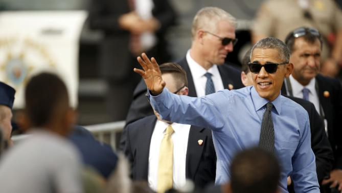 President Barack Obama waves to the crowd before he boards Air Force One at Moffett Federal Airfield Thursday, Feb. 11, 2016, in Mountain View, Calif. Obama will fly to Los Angeles for more DNC fund raisers, as well as a appearance on comedian Ellen DeGeneres' show. (AP Photo/Tony Avelar)