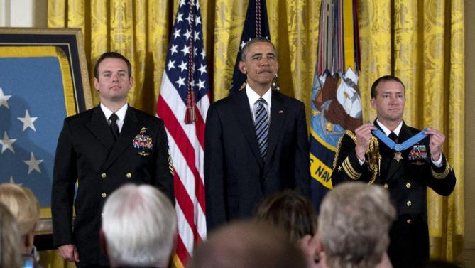 President Barack Obama, center, stands with Senior Chief Special Warfare Operator Edward Byers, left, before presenting him with the Medal of Honor to during a ceremony in the East Room of the White House, in Washington, Monday, Feb. 29, 2016. U.S. Navy. Senior Chief Byers receives the Medal of Honor for his courageous actions while serving as part of a team that rescued an American civilian being held hostage in Afghanistan on December 8-9, 2012. (AP Photo/Carolyn Kaster)