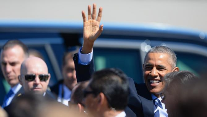 President Barack Obama waves to supporters on the tarmac after arriving on Air Force One at Cecil Airport in Jacksonville, Fla., Friday, Feb. 26, 2016, to visit Saft America factory, which opened in 2011 with help from federal money from economic stimulus package he pushed through Congress in 2009. (AP Photo/Rick Wilson)