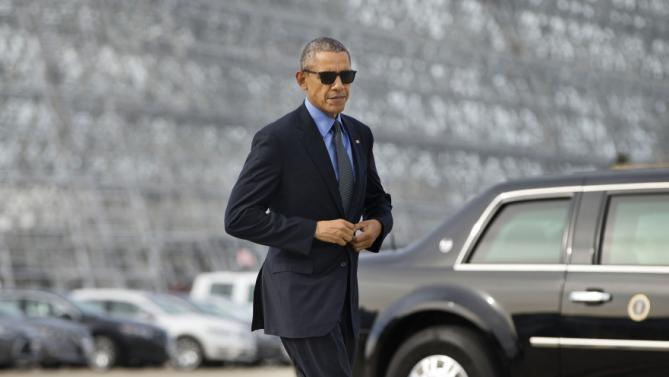 President Barack Obama adjust his suit jacket as he walks across the tarmac before boarding Air Force One at Moffett Federal Airfield in Mountain View, Calif., Thursday, Feb. 11, 2016. Obama is traveling to Los Angeles to tape an appearance on the Ellen DeGeneres Show and attend a pair of private Democratic fundraisers later today. (AP Photo/Pablo Martinez Monsivais)