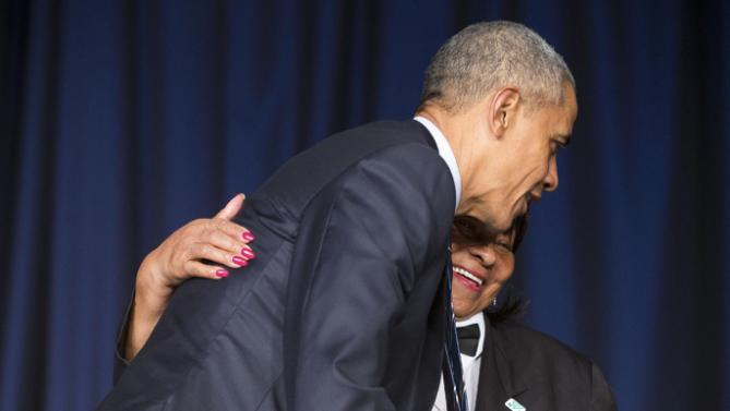President Barack Obama gets up to hug Kitty Casey, an employee at the Washington Hilton, at the National Prayer Breakfast in Washington, Thursday, Feb. 4, 2016. The annual event brings together U.S. and international leaders from different parties and religions for an hour devoted to faith. (AP Photo/Pablo Martinez Monsivais)