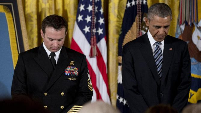President Barack Obama and Senior Chief Special Warfare Operator Edward Byers, left, bow their hears in prayer before the president presents Byers with the Medal of Honor to during a ceremony in the East Room of the White House, in Washington, Monday, Feb. 29, 2016. U.S. Navy Senior Chief Byers receives the Medal of Honor for his courageous actions while serving as part of a team that rescued an American civilian being held hostage in Afghanistan on December 8-9, 2012. (AP Photo/Carolyn Kaster)