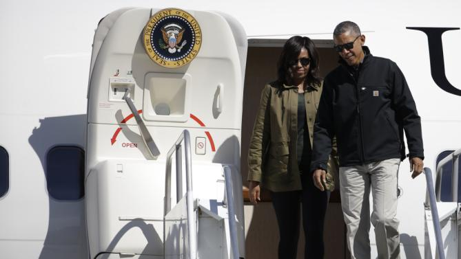 U.S. President Barack Obama accompanied by first lady Michelle get off the plane in Bariloche, Argentina, Thursday, March 24, 2016. Obama is closing his two-day visit to Argentina by spending the afternoon with his family in Bariloche, a picturesque city in southern Argentina, before departing for Washington. (AP Photo/Natacha Pisarenko)