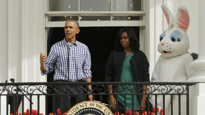 President Barack Obama speaks to the crowd as first lady Michelle Obama and an actor dressed as the Easter Bunny watch on the Truman Balcony during the annual White House Easter Egg Roll in Washington, March 28, 2016. REUTERS/Jonathan Ernst