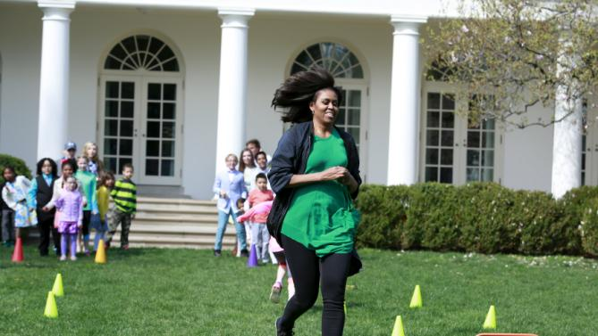 U.S. first lady Michelle Obama runs during a children relay race in the Rose Garden of the White House in Washington at the annual Easter Egg Roll, March 28, 2016. REUTERS/Yuri Gripas