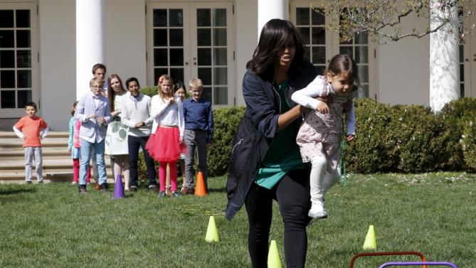 U.S. first lady Michelle Obama helps a girl to complete a relay race in the Rose Garden of the White House in Washington during the annual Easter Egg Roll, March 28, 2016. REUTERS/Yuri Gripas
