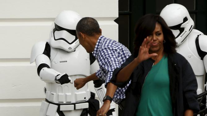 U.S. President Barack Obama (2nd L) fist bumps a costumed Stormtrooper from the Star Wars movies as he and first lady Michelle Obama preside over the annual Easter Egg Roll at the White House in Washington March 28, 2016. REUTERS/Jonathan Ernst