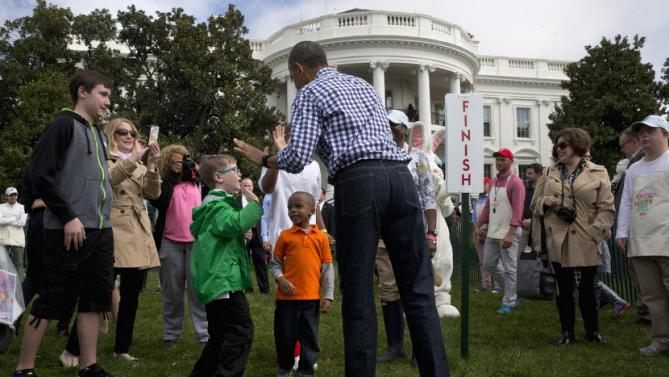 President Barack Obama high fives children at the egg rolling station during the White House Easter Egg Roll at the White House in Washington, Monday, March 28, 2016. Thousands of children gathered at the White House for the annual Easter Egg Roll. This year's event features live music, sports courts, cooking stations, storytelling, and Easter egg rolling. (AP Photo/Jacquelyn Martin)
