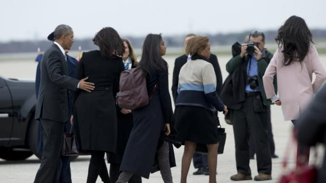 President Barack Obama, from left, with first lady Michelle Obama and their daughters Sasha Obama and Malia Obama, right, and mother-in-law Marian Robinson, fourth from left, walk on the tarmac at Andrews Air Force Base, Md., Sunday, March 20, 2016, to board the Air Force One for a trip Havana, Cuba. Obama is the first U.S. president to visit Cuba in nearly nine decades. (AP Photo/Manuel Balce Ceneta)