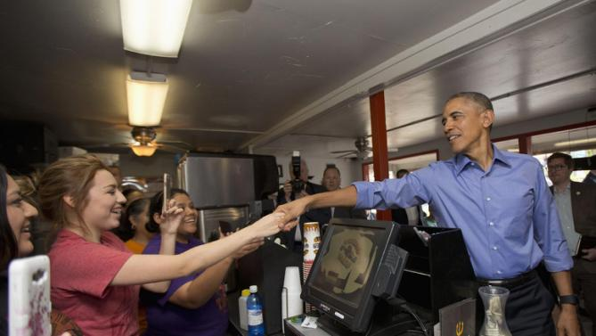 President Barack Obama reaches over the counter to greet employees during an unannounced stop at Torchy's Tacos, Friday, March 11, 2016, in Austin, Texas. Obama traveled to Austin, to speak at South by Southwest Festival (SXSW) and attend 2 Democratic National Committee fundraisers. (AP Photo/Pablo Martinez Monsivais)