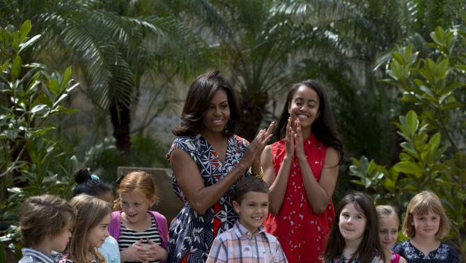 "U.S. First Lady Michelle Obama, center left, and her daughter Malia, center right, clap as they stand with children of U.S. embassy workers after dedicating two magnolia trees and a bench, at a small park beside Ruben Martinez Villena public library in Plaza de las Armas, Old Havana, Cuba, Tuesday, March 22, 2016. The bench bears the inscription in English and Spanish ""A gift to the people of Cuba from Mrs. Michelle Obama, first lady of the U.S., March 2016."" (AP Photo/Rebecca Blackwell)"