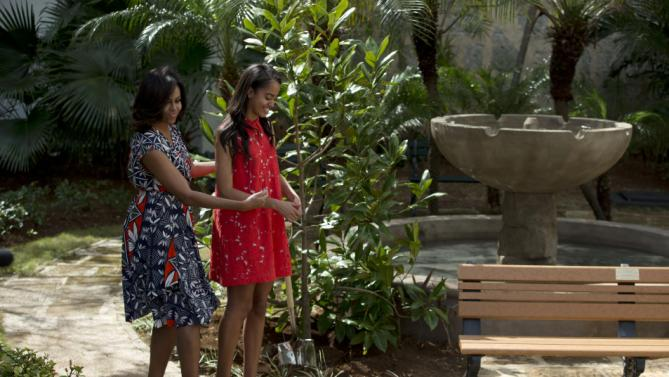"U.S. First Lady Michelle Obama, left, gestures as she and her daughter Malia add a symbolic shovelful of dirt atop a gift of two magnolia trees and a bench, at a small park beside Ruben Martinez Villena public library in Plaza de las Armas, Old Havana, Cuba, Tuesday, March 22, 2016. The bench, made of recycled materials, bears the inscription in English and Spanish ""A gift to the people of Cuba from Mrs. Michelle Obama, first lady of the U.S., March 2016."" (AP Photo/Rebecca Blackwell)"