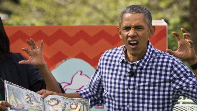"President Barack Obama makes a claw hand and monster face while reading, ""Where The Wild Things Are,"" along with first lady Michelle Obama, during White House Easter Egg Roll at the White House in Washington, Monday, March 28, 2016. Thousands of children gathered at the White House for the annual Easter Egg Roll. This year's event features live music, sports courts, cooking stations, storytelling, and Easter egg rolling. (AP Photo/Jacquelyn Martin)"
