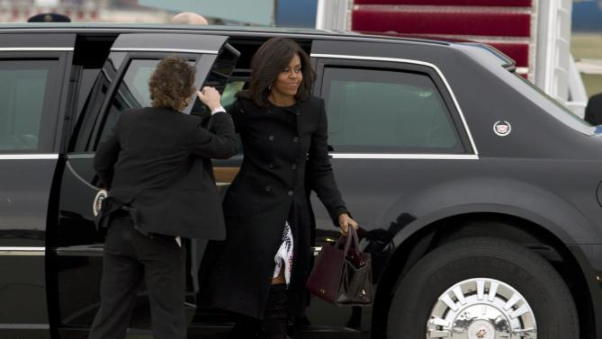First lady Michelle Obama, accompanied by President Barack Obama steps off the limousine upon their arrival to Andrews Air Force Base, before their departure, Sunday, March 20, 2016, en route to Havana, Cuba. Obama and his family are traveling to Havana, the first U.S. president to visit the island in nearly 90 years. ( AP Photo/Jose Luis Magana)