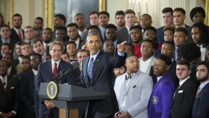 President Barack Obama, center, gestures as he honors the 2015-2016 College Football Playoff National Champion Alabama Crimson Tide during a ceremony in the East Room of the White House, in Washington, Wednesday, March 2, 2016. Also on stage is head coach Nick Saban, left. (AP Photo/Pablo Martinez Monsivais)