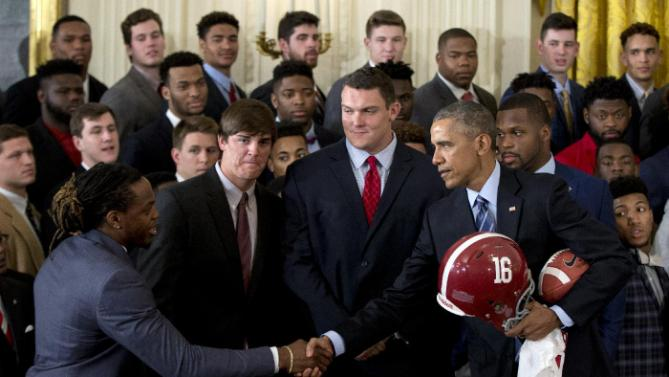 President Barack Obama shakes hands with from left, Alabama Crimson Tide running back Derrick Henry, and teammates quarterback Jake Coker, offensive lineman Ryan Kelly and linebacker Reggie Ragland, as the president is given a football, jersey and helmet during a ceremony to honor the 2015-2016 College Football Playoff National Champion Alabama Crimson Tide football team in the East Room of the White House, in Washington, Wednesday, March 2, 2016. (AP Photo/Carolyn Kaster)