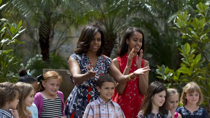 """U.S. First Lady Michelle Obama, center left, thanks embassy workers, as she and her daughter Malia, center right, pose for a picture with their children after dedicating two magnolia trees and a bench, at a small park beside Ruben Martinez Villena public library in Plaza de las Armas, Old Havana, Cuba, Tuesday, March 22, 2016. The bench bears the inscription in English and Spanish """"A gift to the people of Cuba from Mrs. Michelle Obama, first lady of the U.S., March 2016."""" (AP Photo/Rebecca Blackwell)"""