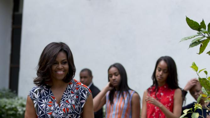 "U.S. First Lady Michelle Obama, left, is accompanied by her daughters Sasha, center, and Malia, as she arrives to dedicate a gift of two magnolia trees and a bench, at a small park beside Ruben Martinez Villena public library in Plaza de las Armas, Old Havana, Cuba, Tuesday, March 22, 2016. The bench bears the inscription in English and Spanish ""A gift to the people of Cuba from Mrs. Michelle Obama, first lady of the U.S., March 2016."" (AP Photo/Rebecca Blackwell)"