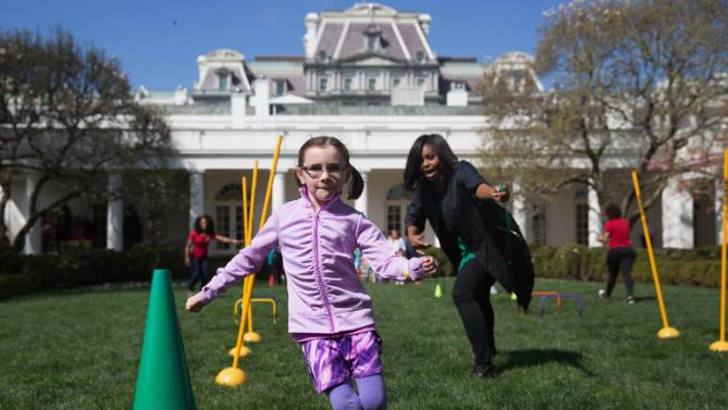 First lady Michelle Obama cheers on children as they run through an obstacle course race in the Rose Garden of the White House in Washington, Monday, March 28, 2016, during the White House Easter Egg Roll. Thousands of children gathered at the White House for the annual Easter Egg Roll. This year's event features  live music, sports courts, cooking stations, storytelling, and Easter egg rolling. (AP Photo/Andrew Harnik)