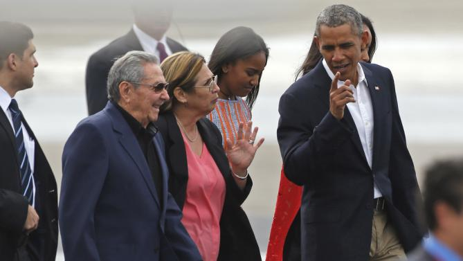 President Barack Obama, right, talks to Cuba's President Raul Castro, left, before boarding Air Force One on his way to Argentina, in Havana, Cuba, Tuesday, March 22, 2016. Behind are Obama's daughters Sasha, second from right, and Malia, partially covered. Obama's visit was a crowning moment in his and Castro's bold bid to restore ties after a half-century diplomatic freeze. (AP Photo/Desmond Boylan)