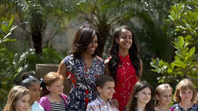 """U.S. First Lady Michelle Obama, center left, and her daughter Malia, center right, pose for a picture with children of U.S. embassy workers after dedicating two magnolia trees and a bench, at a small park beside Ruben Martinez Villena public library in Plaza de las Armas, Old Havana, Cuba, Tuesday, March 22, 2016. The bench bears the inscription in English and Spanish """"A gift to the people of Cuba from Mrs. Michelle Obama, first lady of the U.S., March 2016."""" (AP Photo/Rebecca Blackwell)"""
