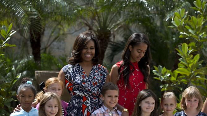 "U.S. First Lady Michelle Obama, center left, and her daughter Malia, center right, stand with children of U.S. embassy workers after dedicating two magnolia trees and a bench, at a small park beside Ruben Martinez Villena public library in Plaza de las Armas, Old Havana, Cuba, Tuesday, March 22, 2016. The bench, made of recycled materials, bears the inscription in English and Spanish ""A gift to the people of Cuba from Mrs. Michelle Obama, first lady of the U.S., March 2016."" (AP Photo/Rebecca Blackwell)"