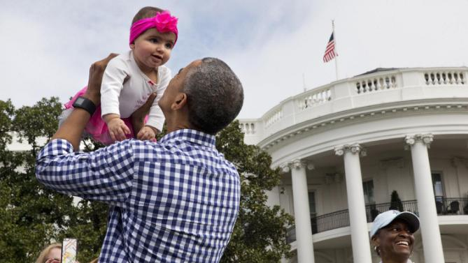 President Barack Obama holds up Stella Muñoz in the air as he visits children at the egg roll station of the White House Easter Egg Roll at the White House in Washington, Monday, March 28, 2016. Thousands of children gathered at the White House for the annual Easter Egg Roll. This year's event features live music, sports courts, cooking stations, storytelling, and Easter egg rolling. (AP Photo/Jacquelyn Martin)