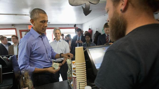 President Barack Obama, accompanied by Austin, Texas Mayor Steve Adler, center,puts a twenty dollar bill in the tip jar after placing his taco order with Torchy's Tacos Aaron Sego, right, during an unannounced stop at Torchy's Tacos, Friday, March 11, 2016, in Austin, Texas. Obama traveled to Austin, to speak at South by Southwest Festival (SXSW) and attend 2 Democratic National Committee fundraisers. (AP Photo/Pablo Martinez Monsivais)
